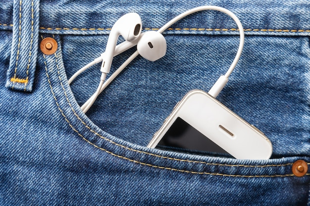 White smartphone with a blank black screen and headphones is in the front pocket of blue jeans