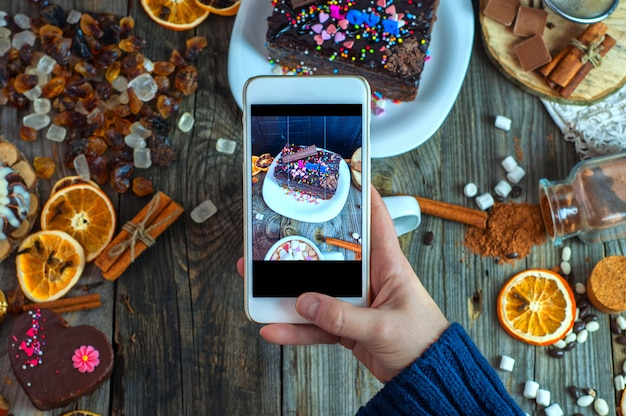 White smartphone in a woman's hand takes a piece of cake and sweets