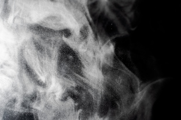 White smoke on a black background. texture of smoke. clubs of white smoke on a dark background for overlay