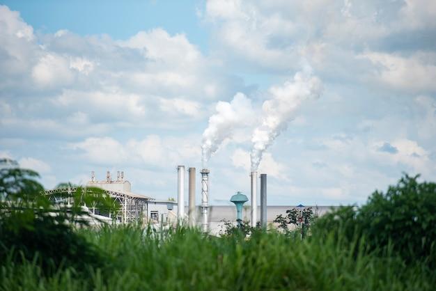 Белый дым выходит из дымовых труб или выхлопных труб заводских дымоходов, выделяет водяной пар, который конденсируется в беловатое облако перед испарением. густой и тяжелый дым выходит из огромной