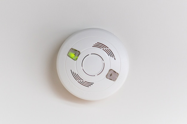 A white smoke detector on a white ceiling