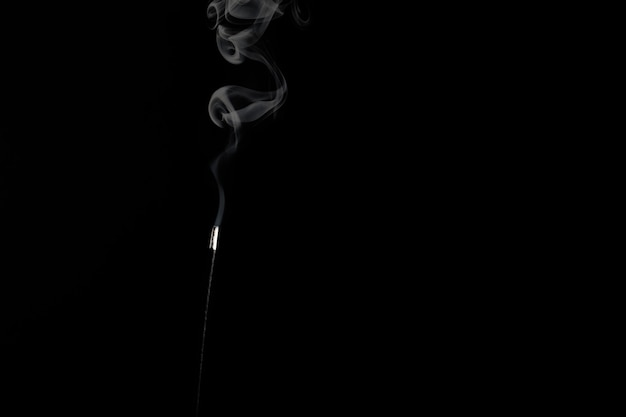 White smoke from an incense stick on a black