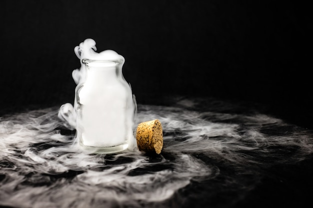 White smoke inside glass bottle at black background