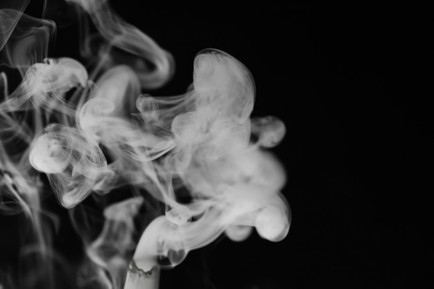 검정색 배경에 흰색 연기입니다. 연기의 질감입니다. 오버레이를 위해 어두운 배경에 흰색 연기 클럽