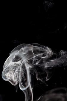 Белый дым на черном фоне.
