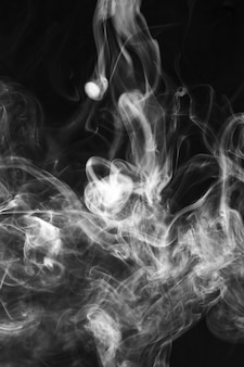 黒い背景に白い煙パターンが広がる