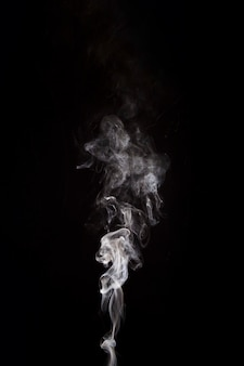 White smoke raising on black background with copy space