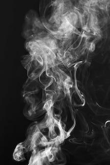 白い煙は黒の背景上の動きを形作る