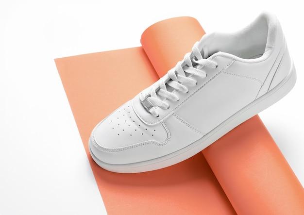 Белый кроссовок на свернутом рулоне оранжевой бумаги на белом фоне. минимализм мода
