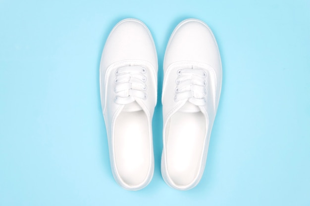 White sneakers on blue background, flat lay .fashion trend shoe,