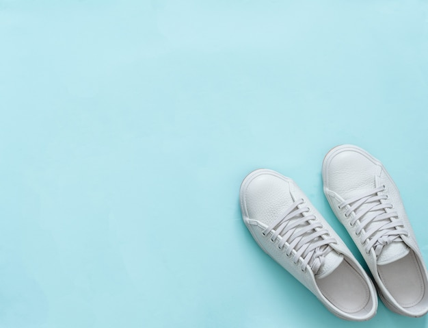White sneakers on blue, copy space, top view