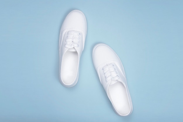 White sneakers on blue, flat lay. fashion trend shoe,  concept shoe shop