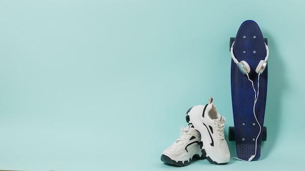 Белые кроссовки, синий скейтборд и белые наушники на синей поверхности