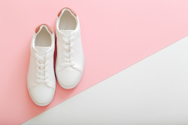 White sneakers, female white leather shoes with laces on pink background. pair of stylish sneakers comfortable sportswear hipster womens shoes. top view copy space.