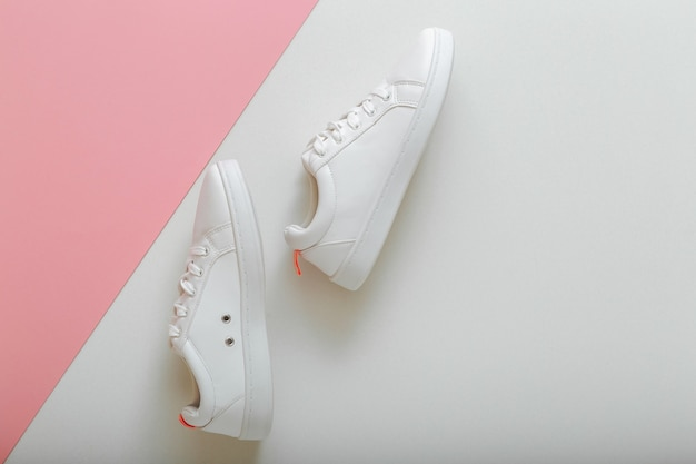 White sneakers, female white leather shoes with laces on pink background. pair of stylish sneakers comfortable sportswear hipster womens shoes. top view with copy space.