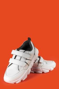 色付きの背景、コピースペースのフィットネスやスポーツのための白いスニーカー
