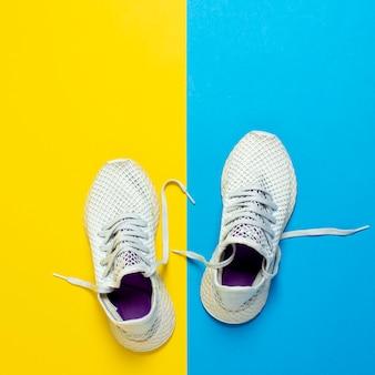 抽象的な黄色と青の表面で実行するための白いスニーカー。ランニング、トレーニング、スポーツの概念。平方。フラット横たわっていた、トップビュー