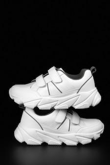 暗い背景のスポーツのためのティーンエイジャーのための白いスニーカー、コピースペース