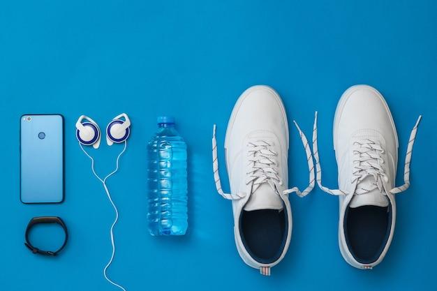 Белые кроссовки, наушники, умный браслет и бутылка с водой на синем фоне. спортивный стиль. плоская планировка. вид сверху.