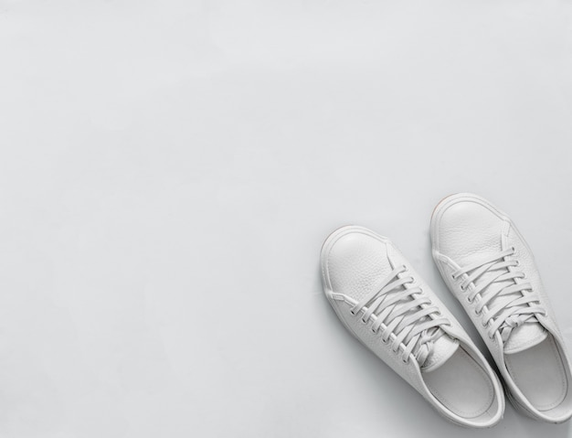 White sneakers on light background, copy space