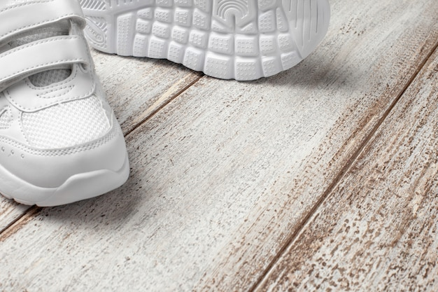 White sneakers on a light background with a place to copy text or design a pair of fashionable child...