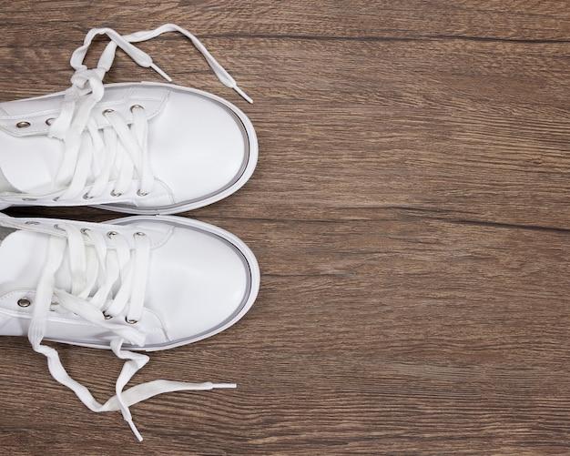 Белые кроссовки на темной деревянной поверхности. обувь для женщин в стиле спортивной моды. копировать пространство