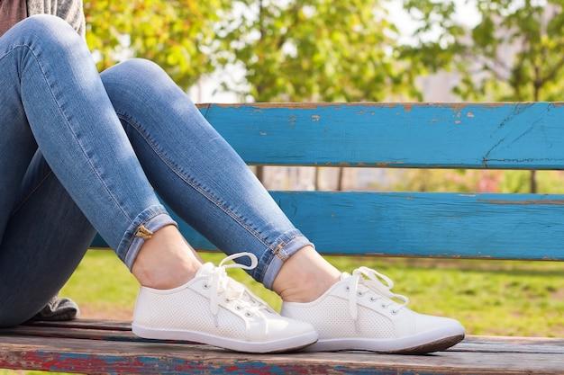 Белые кроссовки на женских ногах в синих джинсах на синей скамейке и зеленом фоне растений.