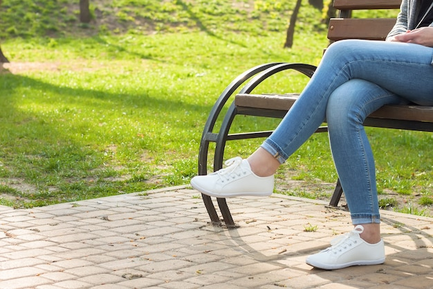 Белые кроссовки на женских ногах в синих джинсах на фоне асфальта и зеленой травы.