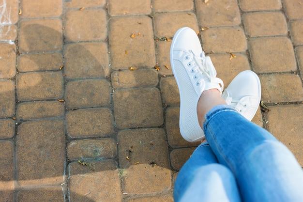 Белые кроссовки на женских ногах в синих джинсах на фоне асфальта и зеленых растений.