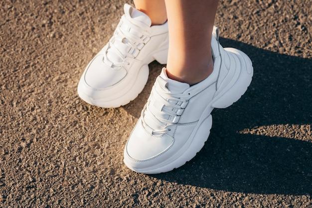 アスファルトの女の子の足に白いスニーカー