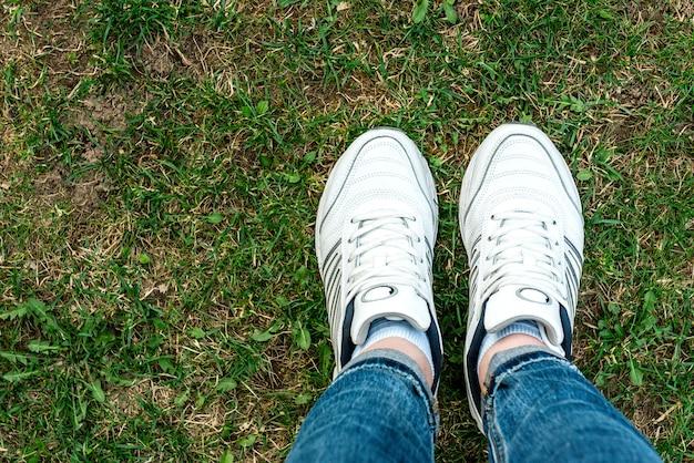 草の背景に白いスニーカー。健康的な生活様式。スポーツ。