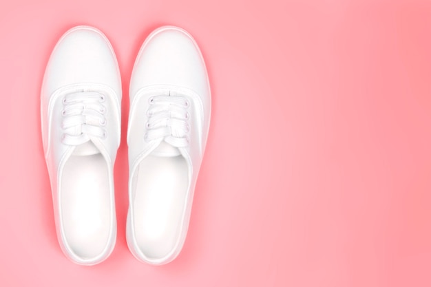 White sneakers on a pink background close-up, copy spacefashion trend of shoes.