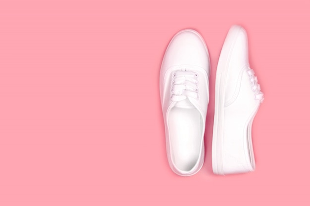 White sneakers on pink background