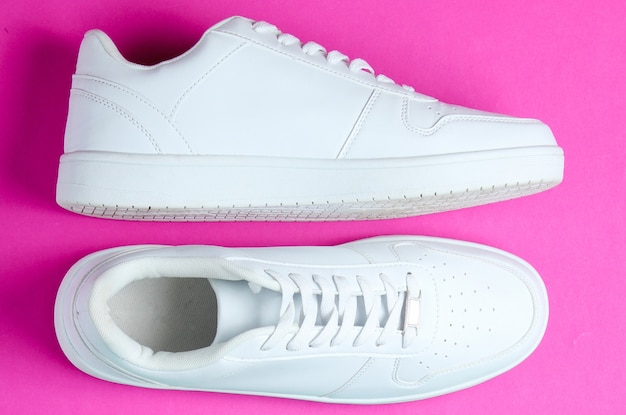 Белые кроссовки, пластиковые гантели на двухцветном фоне. концепция спорта. вид сверху