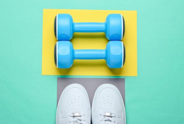 Белые кроссовки, пластиковые гантели на цветной стол. спортивная концепция. вид сверху