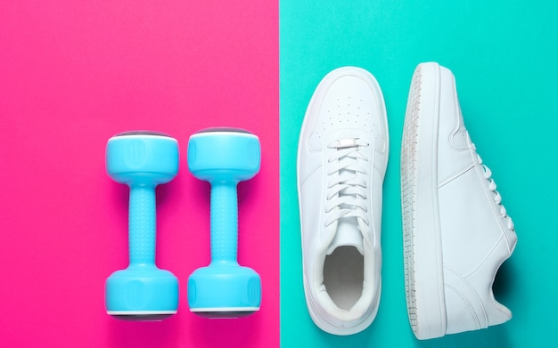White sneakers, plastic dumbbells on a two-color background. sport concept. top view