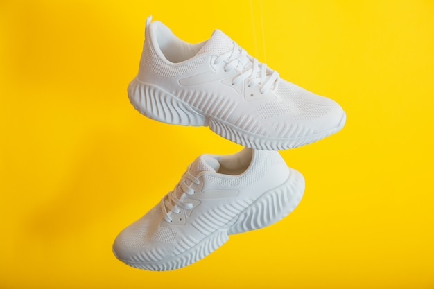 White sneakers shoes fly on yellow color background. pair of sport male sneakers. levitation footwear on yellow wall.