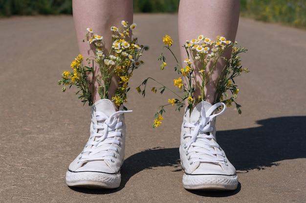 White sneakers shoes walking on asphalt, canvas shoes walking on concrete