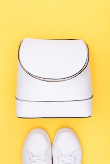White sneakers and white backpack on yellow