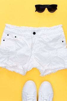 White sneakers and white shorts on yellow.