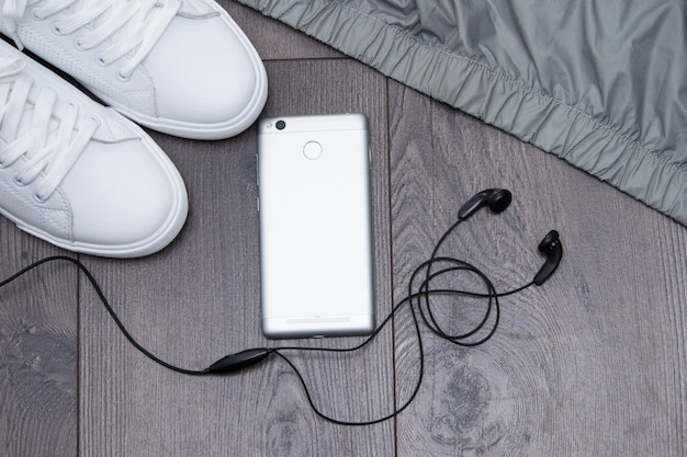 White sneakers with phone, headphones, jacket on grey brown wooden background. flat lay, copy space.