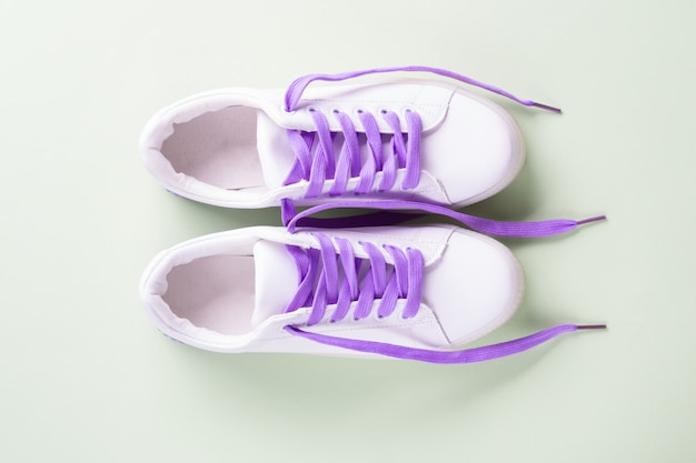 White sneakers with purple laces on green