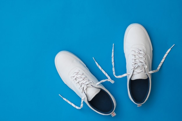 White sneakers with untied laces on a blue surface