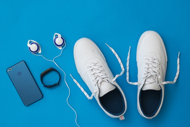 White sneakers with untied laces, smartphone, headphones and smart bracelet on blue surface