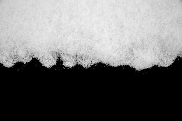 黒の背景に分離された白い雪。デザインのための冬の要素。高品質の写真