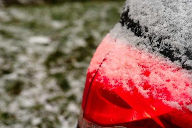 冬季の車のヘッドライトの表面に白い雪。車のリアライトがクローズアップ。