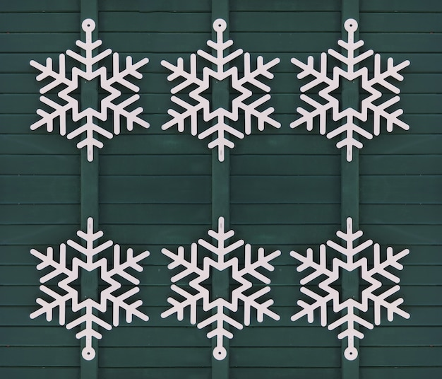 緑の木製のドアのクリスマスの装飾に白い雪の結晶