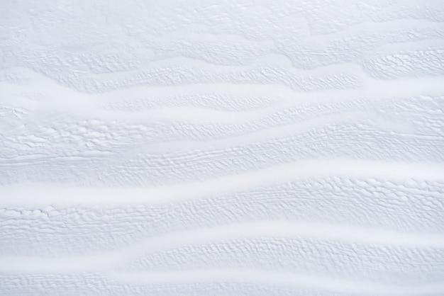 白い雪の背景。雪の抽象的なテクスチャ