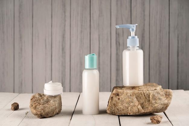 天然石と木製の背景に白い石鹸とクリーム色の容器