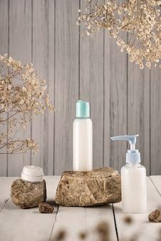 天然石に花が付いている白い石鹸とクリーム色の容器